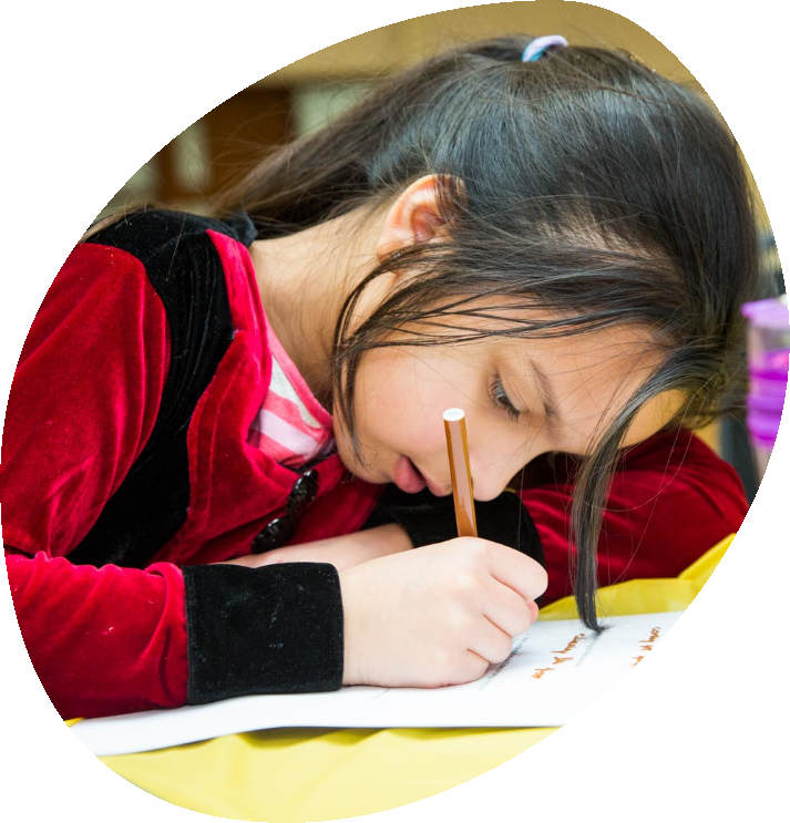 child writing down on paper